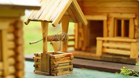 Model of the  wooden house with a draw-well Stock Photos