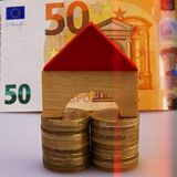 Model of a wooden house sits on piles of euro coins on the backg. Round of a fifty euro banknote. Closeup. Currency of the Euro Union Stock Photography