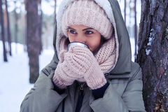 Model wrapped up in a warm winter clothes, drinking tea on a col Stock Photography