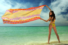 Model in yellow bikini holding pareo. On the wind at tropical location Royalty Free Stock Photo