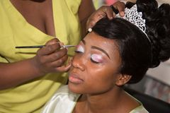 Young pretty american black woman getting her eyes make up done by professional artist using brush applying eyeshadow for wedding. Model young pretty american stock photos
