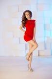 Model z długie włosy w czerwieni sukni z krzesłem Fala kędziory Hairst Obraz Royalty Free