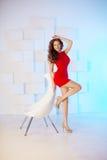 Model z długie włosy w czerwieni sukni z krzesłem Fala kędziory Hairst Zdjęcia Stock