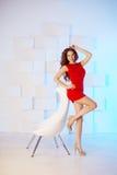 Model z długie włosy w czerwieni sukni z krzesłem Fala kędziory Hairst Obraz Stock