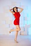 Model z długie włosy w czerwieni sukni z krzesłem Fala kędziory Hairst Zdjęcia Royalty Free