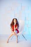 Model z długie włosy w czerwieni sukni z krzesłem Fala kędziory Hairst Obrazy Stock
