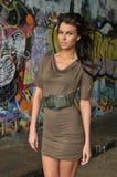 Modelandningsbanamodell som poserar på lägen med grafitti på väggarna Arkivfoto