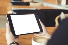 Modelbeeld die van bedrijfsvrouwen` s handen zwarte tabletpc met lege witte het scherm en koffiekop op houten lijst houden Royalty-vrije Stock Afbeelding