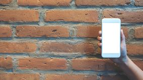 Modelbeeld die van hand en witte mobiele telefoon met het lege scherm met bakstenen muur houden opheffen Stock Afbeeldingen