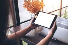 Modelbeeld die van handen zwarte tabletpc met lege witte het scherm en bloemvaas op houten lijst houden Stock Fotografie