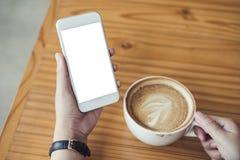 Modelbeeld die van vrouwen` s handen witte mobiele telefoon met het lege scherm en witte koffiekop van hete latte op houten lijst Royalty-vrije Stock Afbeelding