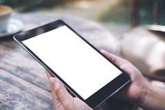 Modelbeeld die van vrouwen` s handen zwarte tabletpc met het witte lege scherm met uitstekende houten lijst houden Royalty-vrije Stock Afbeeldingen
