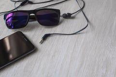 Modelbeeld van bril rubber de oortelefoonsheerser van het notitieboekjepotlood met zwarte mobiele telefoon en het lege witte sche stock foto