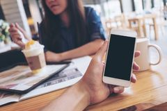 Modelbeeld van een man ` s hand die witte mobiele telefoon met het lege zwarte scherm in de moderne koffie en onduidelijk beeldkr Royalty-vrije Stock Afbeeldingen