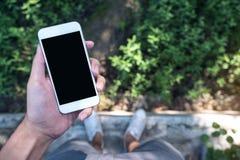 Modelbeeld van een mensen` s hand die witte mobiele telefoon met het lege zwarte scherm houden terwijl status op concrete vloer m Stock Afbeeldingen