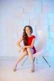 Modele con el pelo largo en vestido rojo con la silla Rizos Hairst de las ondas Foto de archivo