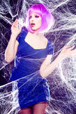 Modele con la peluca púrpura y el maquillaje intenso atrapados en un Web de araña Imagen de archivo