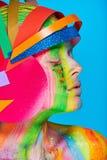 Modele con maquillaje abstracto colorido en casco multicolor Imágenes de archivo libres de regalías