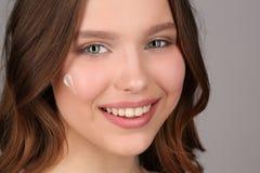 Modele con maquillaje y crema en su cara Cierre para arriba Fondo gris Fotografía de archivo