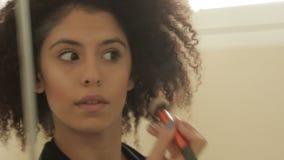 Modele con un peinado afro muy rizado que pone maquillaje metrajes