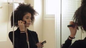 Modele con un peinado afro muy rizado que pone maquillaje almacen de metraje de vídeo