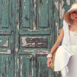 Modele contra puerta del vintage en el vestido blanco y el accessorie elegante Imagen de archivo