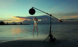 Modele en bikini con la presentación del collar coralino atractiva en la playa vacía Imagenes de archivo