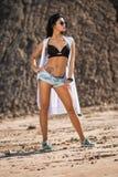 Modele en el bikini negro que presenta en rocas de una arena Imágenes de archivo libres de regalías