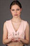 Modele en el vidrio que se sostiene superior del rosa de agua Cierre para arriba Fondo gris Foto de archivo libre de regalías
