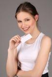 Modele en la camiseta blanca que presenta con el resbalón del papel Cierre para arriba Fondo gris Imagen de archivo