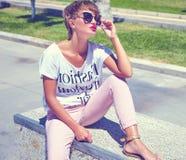 Modele en la ropa casual del inconformista del verano que presenta en fondo de la calle Imagenes de archivo