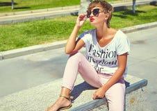 Modele en la ropa casual del inconformista del verano que presenta en fondo de la calle Foto de archivo libre de regalías