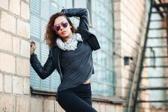 Modele en las gafas de sol, chaqueta de cuero del negro, vaqueros Presentación cerca de una pared de ladrillo roja fotografía de archivo