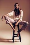 Modele en pantalones superiores y rayados del blanco en silla Imagen de archivo libre de regalías