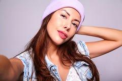 Modele en ropa casual de los vaqueros del verano sin maquillaje en la gorrita tejida púrpura que hace la foto del selfie en smart Fotos de archivo