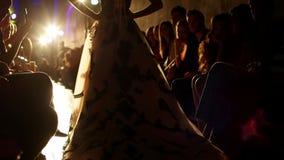 Modele en un vestido de bola lujoso con los proyectores