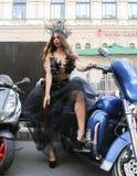 Modele en un vestido transparente que presenta en motocicleta azul Imagen de archivo