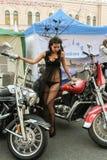 Modele en un vestido transparente que presenta en una motocicleta roja Imagen de archivo libre de regalías
