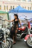 Modele en un vestido transparente que presenta en una motocicleta roja Fotos de archivo