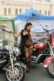Modele en un vestido transparente que presenta en una motocicleta roja Imagenes de archivo