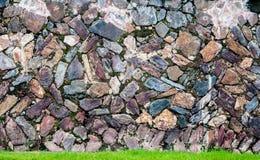 Modele la superficie real agrietada desigual decorativa de la pared de piedra con el cemento y la hierba verde Fotos de archivo