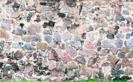 Modele la superficie real agrietada desigual decorativa de la pared de piedra con el cemento y la hierba verde Imagen de archivo