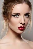 Modelez avec le rétro renivellement, les languettes de cru et l'eye-liner rouges image stock