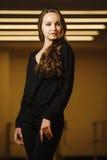 Modelez dans la pose élégante de vêtements noirs dans le cadre images stock