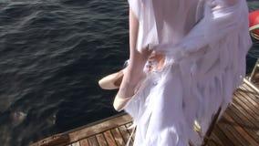 Modelez dans le costume blanc des pointes de vêtements d'ange sur le bateau près de l'eau en Mer Rouge banque de vidéos