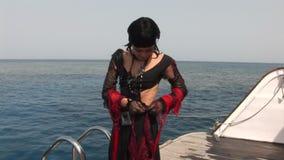 Modelez dans le costume blanc du pirate sur le bateau près de l'eau en Mer Rouge banque de vidéos