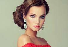 Modelez dans un sensible composent, habillé dans une robe rouge photo libre de droits