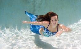 Modelez dans une piscine portant un mermaid& x27 ; queue de s Photographie stock libre de droits