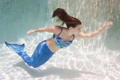 Modelez dans une piscine portant un mermaid& x27 ; queue de s Photos libres de droits