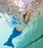 Modelez dans une piscine portant un mermaid& x27 ; queue de s Image libre de droits